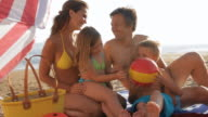 family sitting together under beach umbrella playing with ball