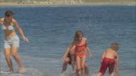 WS PAN MS Family splashing in ocean and running along beach / Phippsburg, Maine, USA
