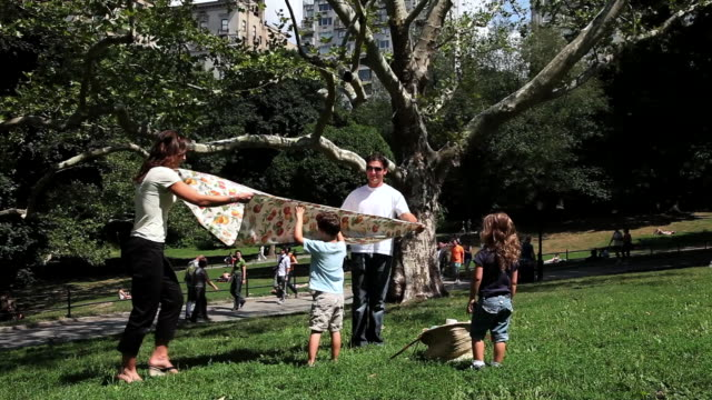 MS Family spreads sheet for picnic at  sailboat pond in park / New York, New York, United States