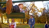 SLO MO Family swinging in the park