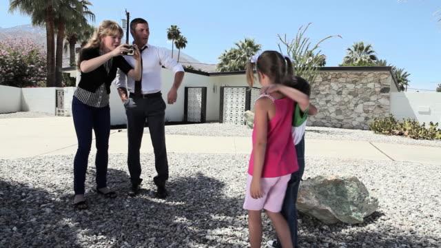 Family taking photographs outside home