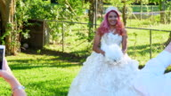 MS PAN Family taking photos with smartphones of young woman in quinceanera gown in backyard