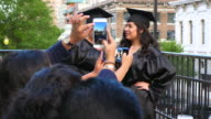 MS PAN Family taking picture of two female graduates during celebration meal on restaurant deck