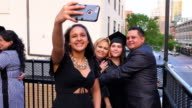 MS Family taking selfie with smartphone while celebrating daughters graduation on restaurant deck
