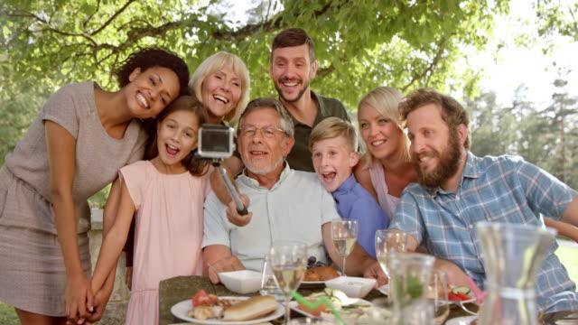 SLO MO familie nemen van selfies op de picknicktafel