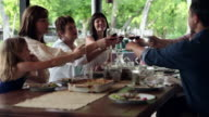 MS family toasting at dinner table outdoors on porch of home