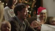 MS SELECTIVE FOCUS Family unwrapping Christmas gifts / Cedar Hills,Utah,USA