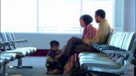 A family waits in chairs at the gate for their flight.