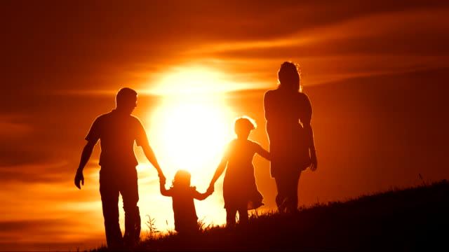 HD RALLENTATORE: Famiglia a piedi sul prato al tramonto