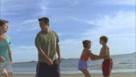LA MS Family walking and playing along beach near water's edge / Phippsburg, Maine, USA