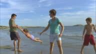 LA WS Family walking and playing along beach near water's edge / Phippsburg, Maine, USA