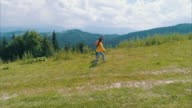 Family walking in mountains on sunny day