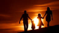HD SLOW MOTION: Family Walking On A Meadow At Sunset