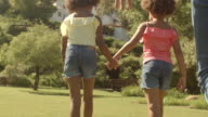 Family walking past camera in park holding hand