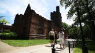 Family walks near a historic stone building on Princeton University campus