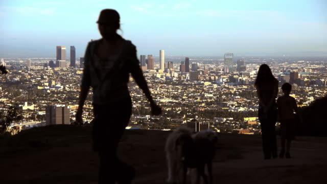 A family walks their dog on a mountain near Los Angeles.