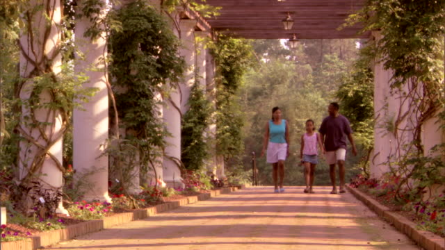 A family walks toward the viewer on a brick pathway among flower gardens.