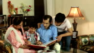 Family watching picture album at home, Delhi, India
