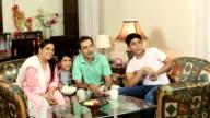 Family watching television at home, Delhi, India
