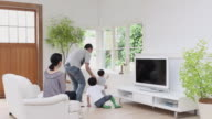 WS Family with baby boy (12-17 months) and son (6-7) watching TV in living room / Setagaya, Tokyo, Japan