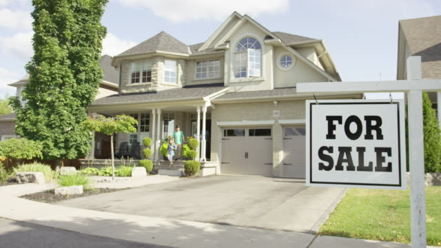 Family with 'For Sale' real estate sign