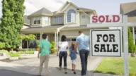 """Famiglia con """"per la vendita, venduti"""" Cartello di agenzia immobiliare"""