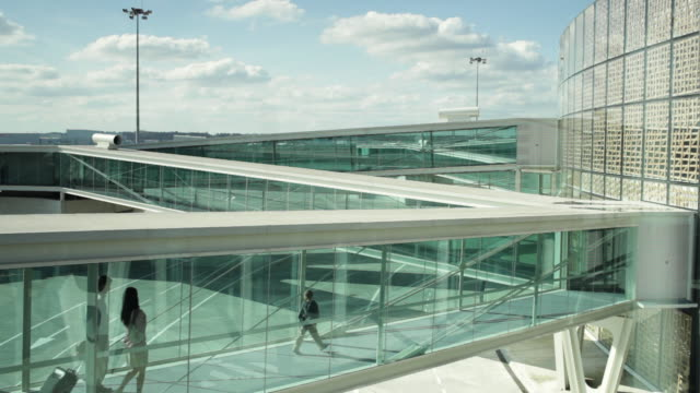 WS Family with son (8-9) walking along glass walkway towards airport building / Toulouse, Haute-Garonne, France
