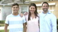 Family with teenage son in front yard