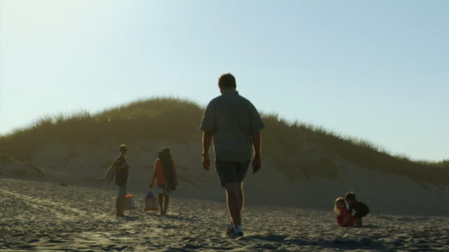MS, Family with two children(4-5, 6-7) walking on sand dune, rear view, North Truro, Massachusetts, USA