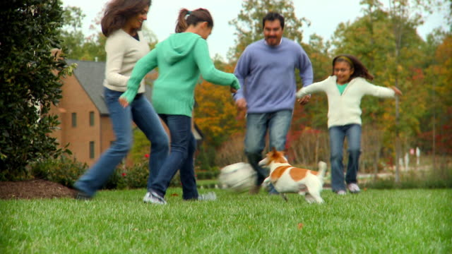CU, TU, TD, Family with two daughters (6-7, 10-11) and Jack Russell terrier playing soccer in garden, Richmond, Virginia, USA