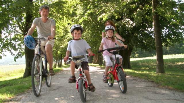 HD: Familie mit zwei Kindern im Park, beim Radfahren