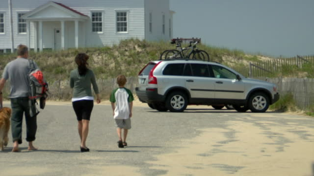 WS, Family with two sons (8-9, 10-11) and dog getting into car parked in front of cottage house, Provincetown, Cape cod, Massachusetts, USA
