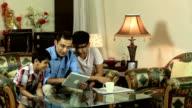 Family working on digital tablet, Delhi, India
