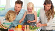 Family working together to prepare a salad