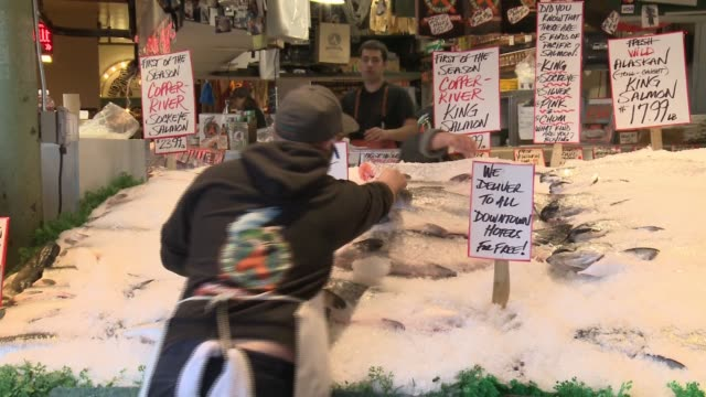 Famous fish sellers at Seattle's Pike Place market throwing fish across their stall