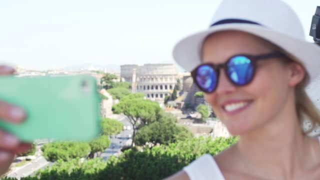 Famous Roman landmark - Coliseum. Tourist woman making selfie