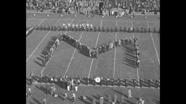 WS fanfilled Michigan Stadium / Michigan marching band on the field makes a dog house /Michigan alumni form an M / Michigan State Spartans and Yale...