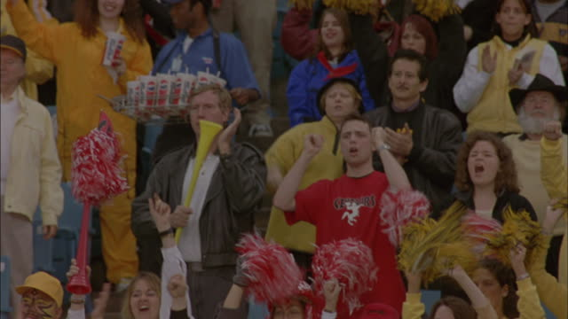 Fans raise their hands in the air and cheer while watching a football game.