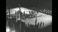 far tilt of a Monegasque band and dancers performing in the courtyard of Monaco's Palace / banks of lights atop palace with illuminated windows / VS...