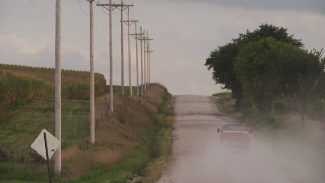 Farm pick up truck drives away from camera down a dusty gravel road line with telephone poles.