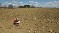 Farmer checks soil conditions in newly tilled field.