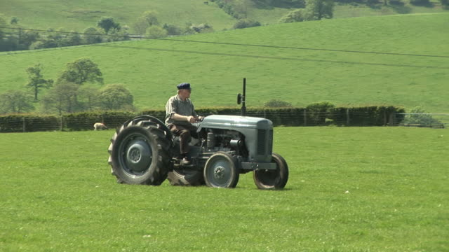 Farmer driving old vintage tractor in farm field (Agriculture)