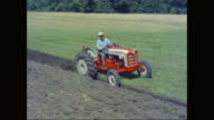WS TS Farmer driving tractor while roller harrow ploughing in field / United States