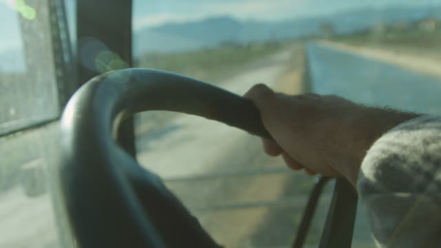 A farmer guy drives a tractor. Close up of his strong hands.