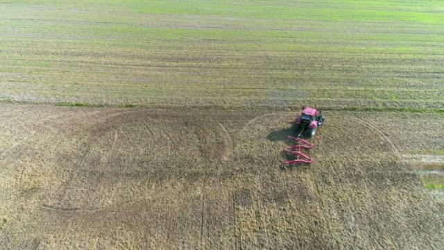 Farmer Harrowing Crop Field In Late Summer