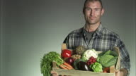 A farmer holding a case of vegetables.
