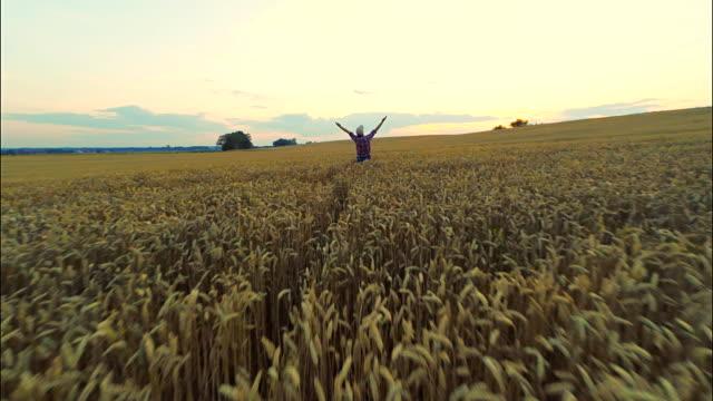 AERIAL Farmer hält seine Arme hoch
