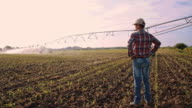 DS Farmer looking at agricultural sprinklers in field