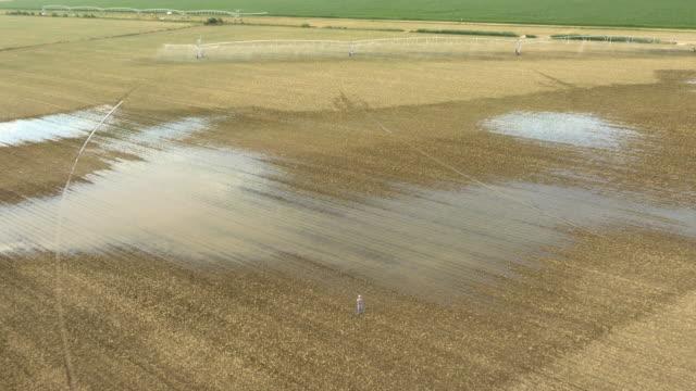 AERIAL Farmer looking at devastated field