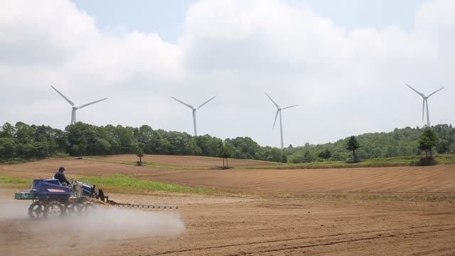 A farmer operates a tractor on a field in front of wind turbines at Electric Power Development Co's Nunobiki wind farm in Koriyama Fukushima Japan on...